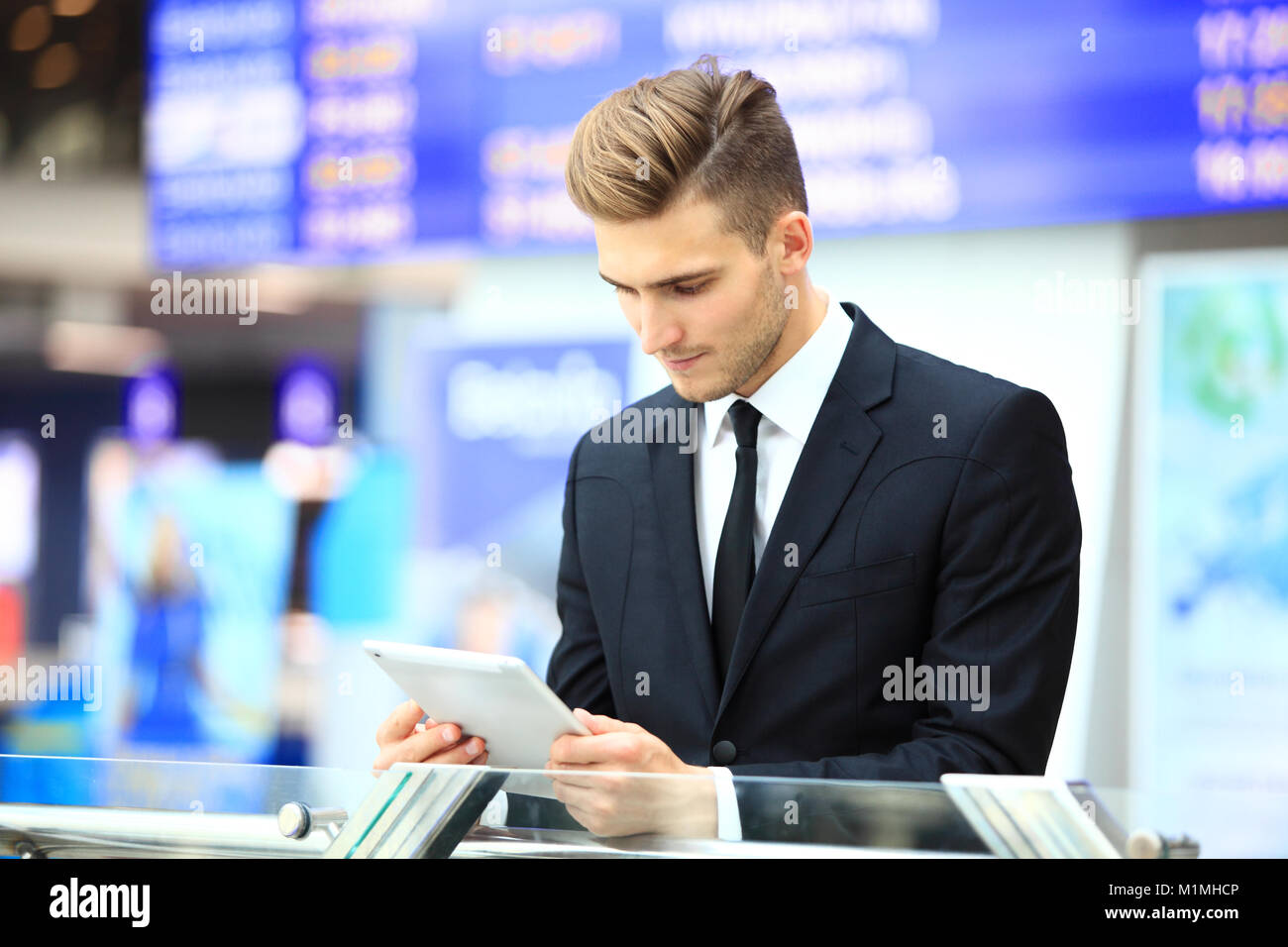 Businessman Using Digital Tablet In Airport Departure Lounge - Stock Image