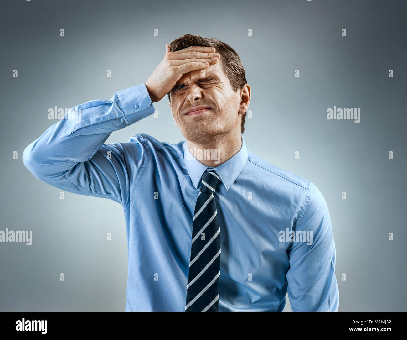 Man holding his head in pain. Photo of man in shirt and tie grimacing in pain on gray background. Medical concept - Stock Image