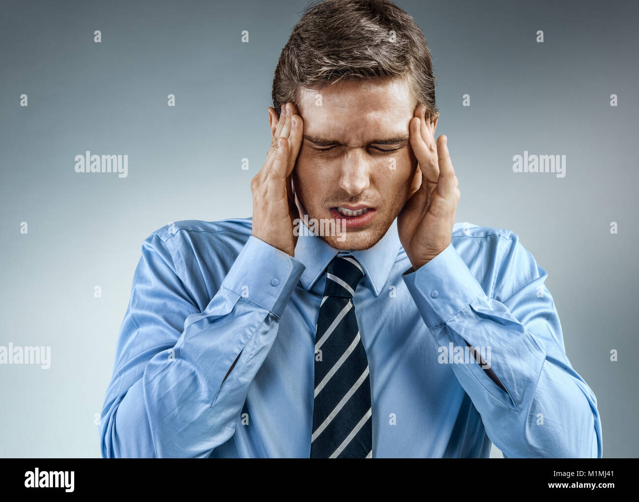 Young businessman with pain in his temples. Photo of man suffering from stress or a headache grimacing in pain. - Stock Image