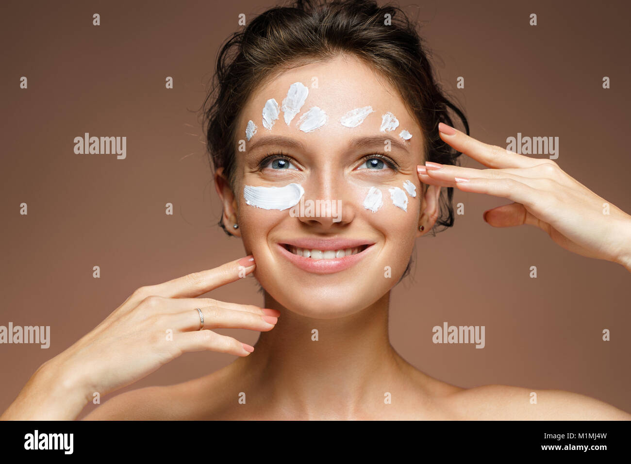 Young woman with moisturizing cream. Photo of beautiful brunette woman touching her face on brown background. Skin - Stock Image