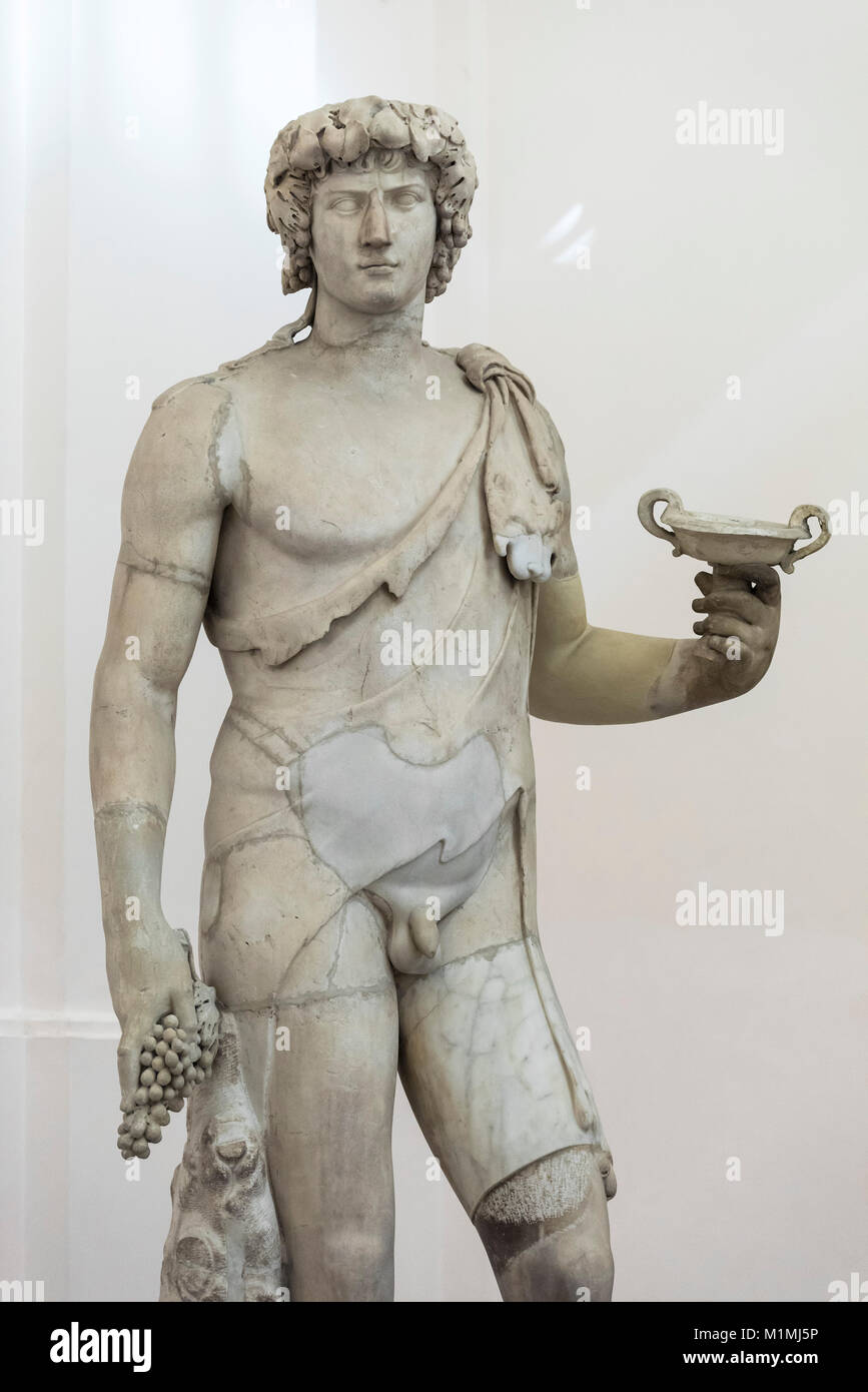 Naples. Italy. Antinous-Bacchus holding a bunch of grapes and a kylix, Roman sculpture, 2nd century A.D.  Museo - Stock Image