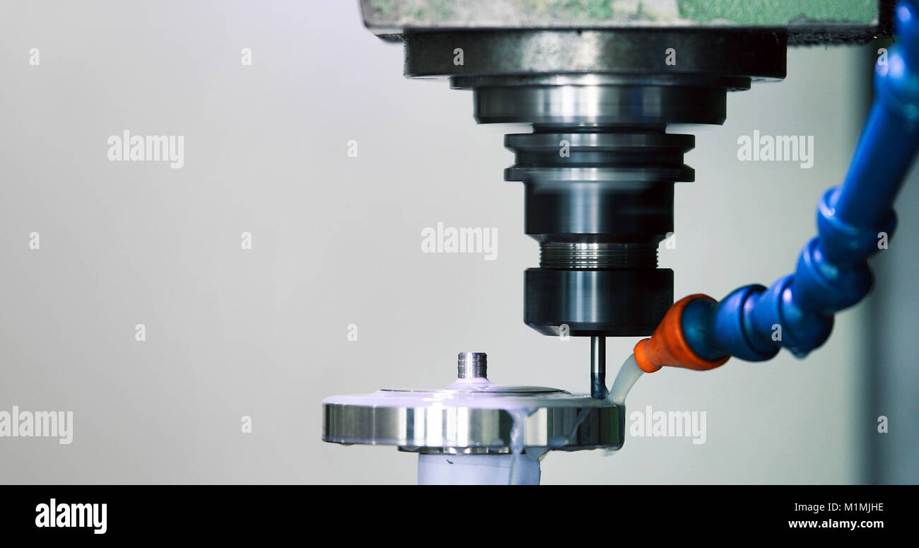 Precision industrial CNC machining of metal detail by mill at factory - Stock Image
