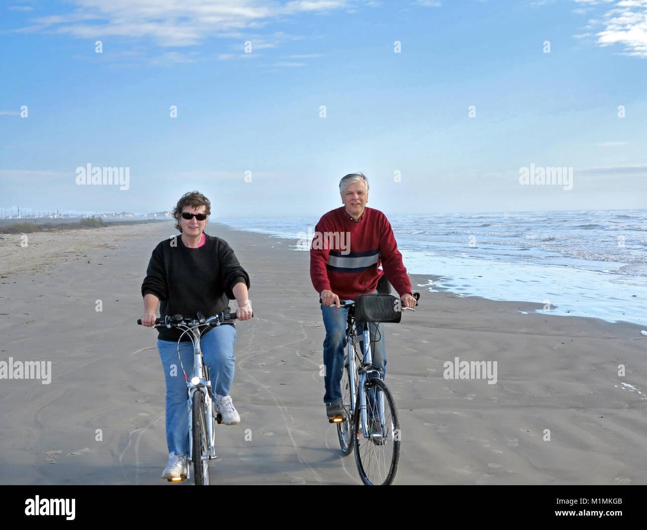 Active couple bicycling on Mustang Island, Corpus Christi, Texas, USA - Stock Image