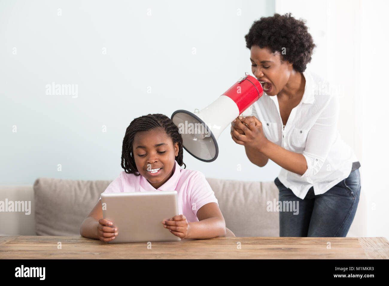 Mother Shouting At Her Daughter Holding Digital Tablet In A Megaphone At Home - Stock Image