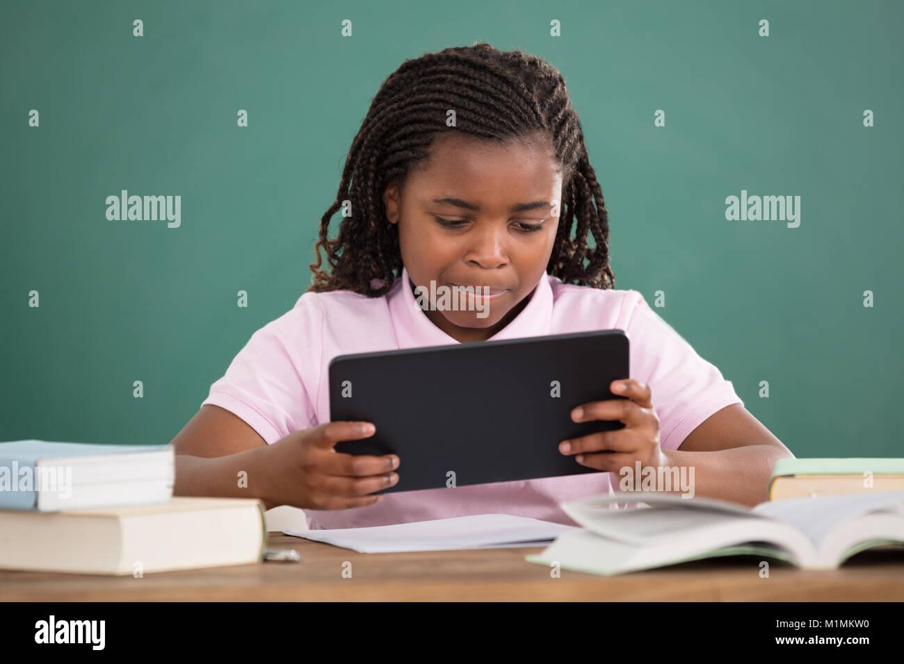 Schoolgirl Using Digital Tablet While Studying Against Chalkboard - Stock Image