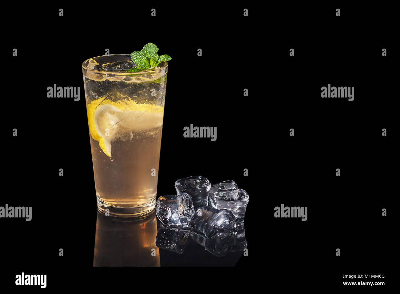alcohol cocktail with lemon and mint on a black background - Stock Image