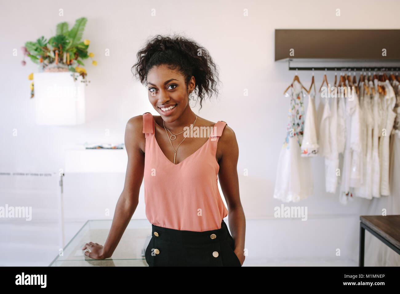 Female fashion designer standing at her desk in her boutique. Female dress designer in her cloth shop with designer - Stock Image