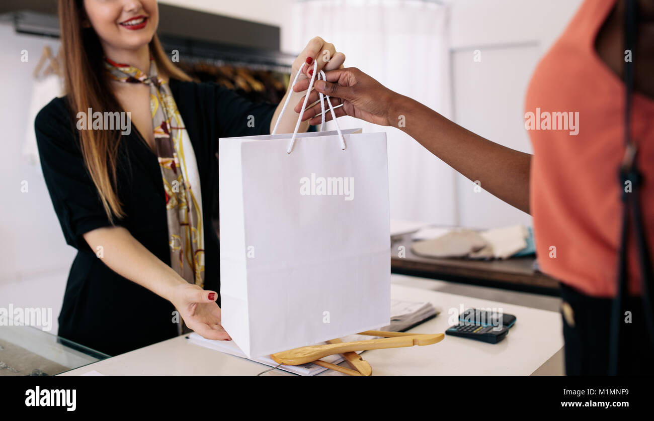 Customer shopping designer wear at a fashion boutique. Woman entrepreneur handing over shopping bag to the customer. - Stock Image