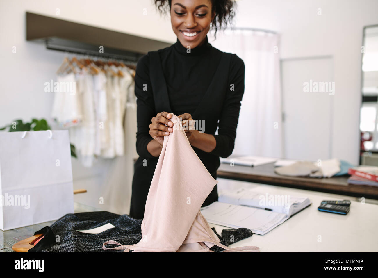 Woman entrepreneur showing designer clothes to a customer at her fashion boutique. Female storekeeper packing clothes - Stock Image
