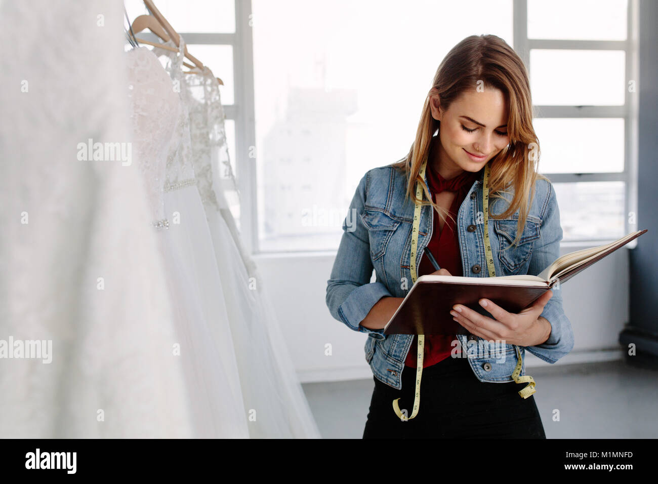 Female fashion designer working in bridal wear store and writing in a diary. Female bridal store owner in her boutique. - Stock Image