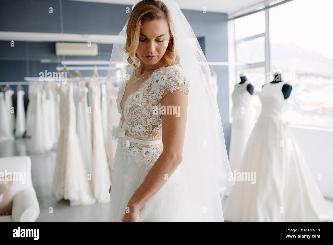 Beautiful Young Woman Trying On Bridal Gown In Wedding Fashion Shop