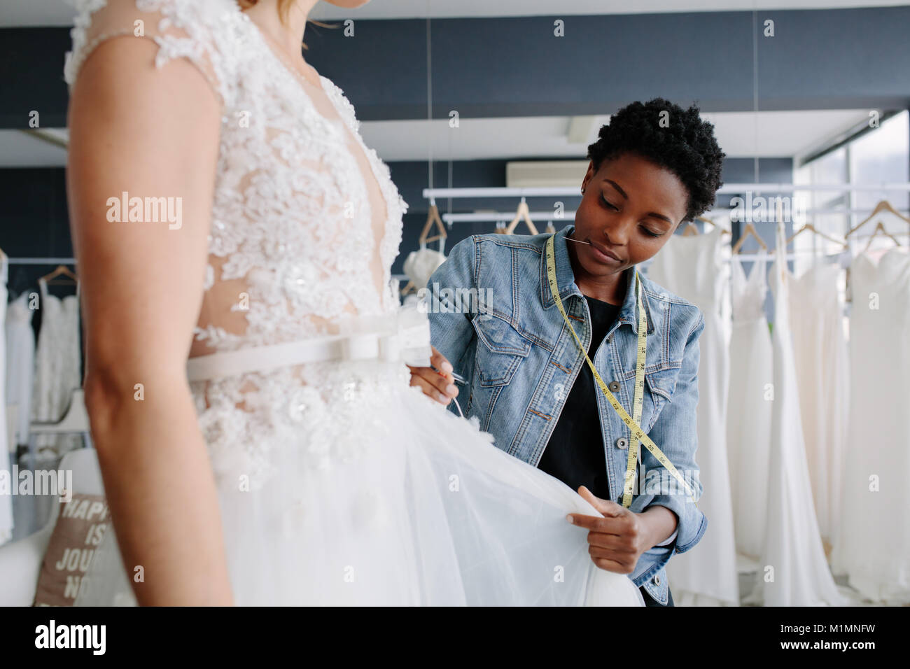 Professional wedding dress designer fitting bridal gown to woman in her store. Woman making adjustments to bridal - Stock Image