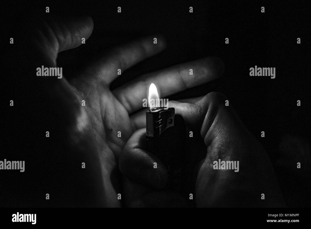 Man hands lights a lighter in the dark - Stock Image