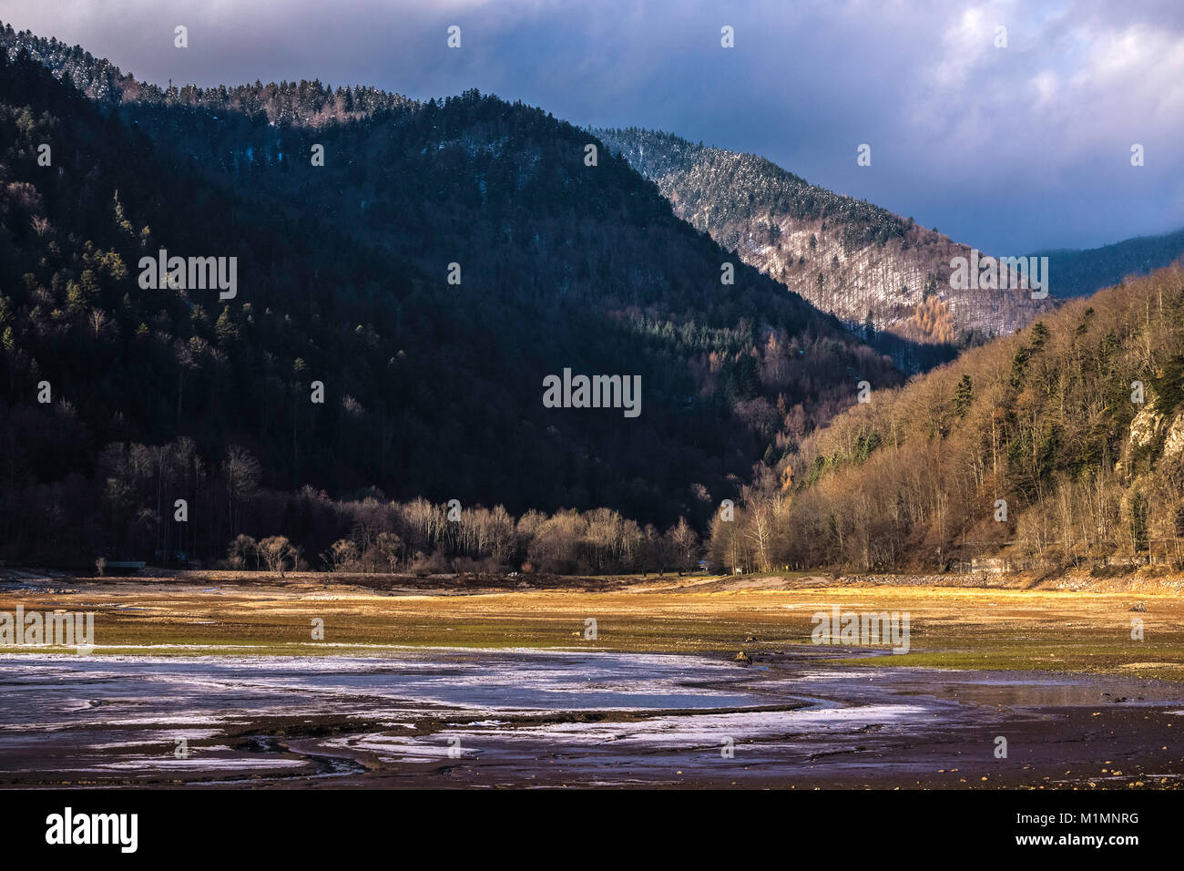 Landscape of the Kruth-Wildenstein Lake and the mountains surrounding it in the Vosges on a sunny and cloudy day - Stock Image