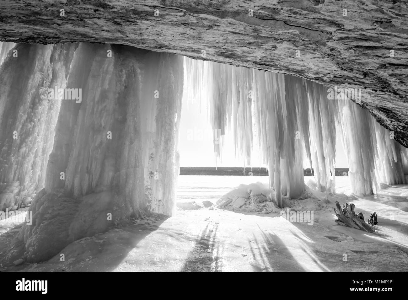 A sun burst shines around an ice column curtain on Grand Island near Munising Michigan in winter - Stock Image