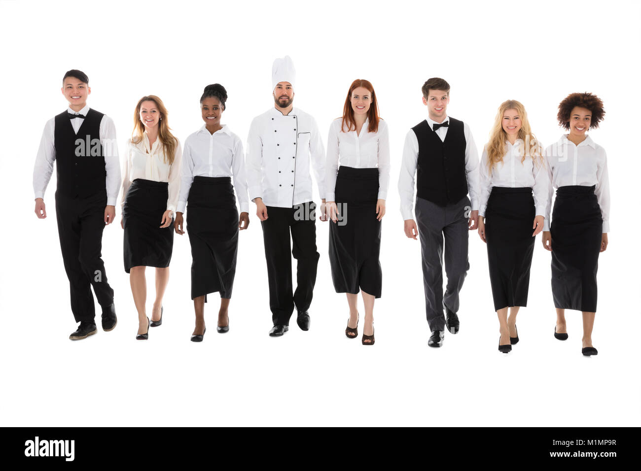 Portrait Of Happy Restaurant Staff Walking Against White Background - Stock Image