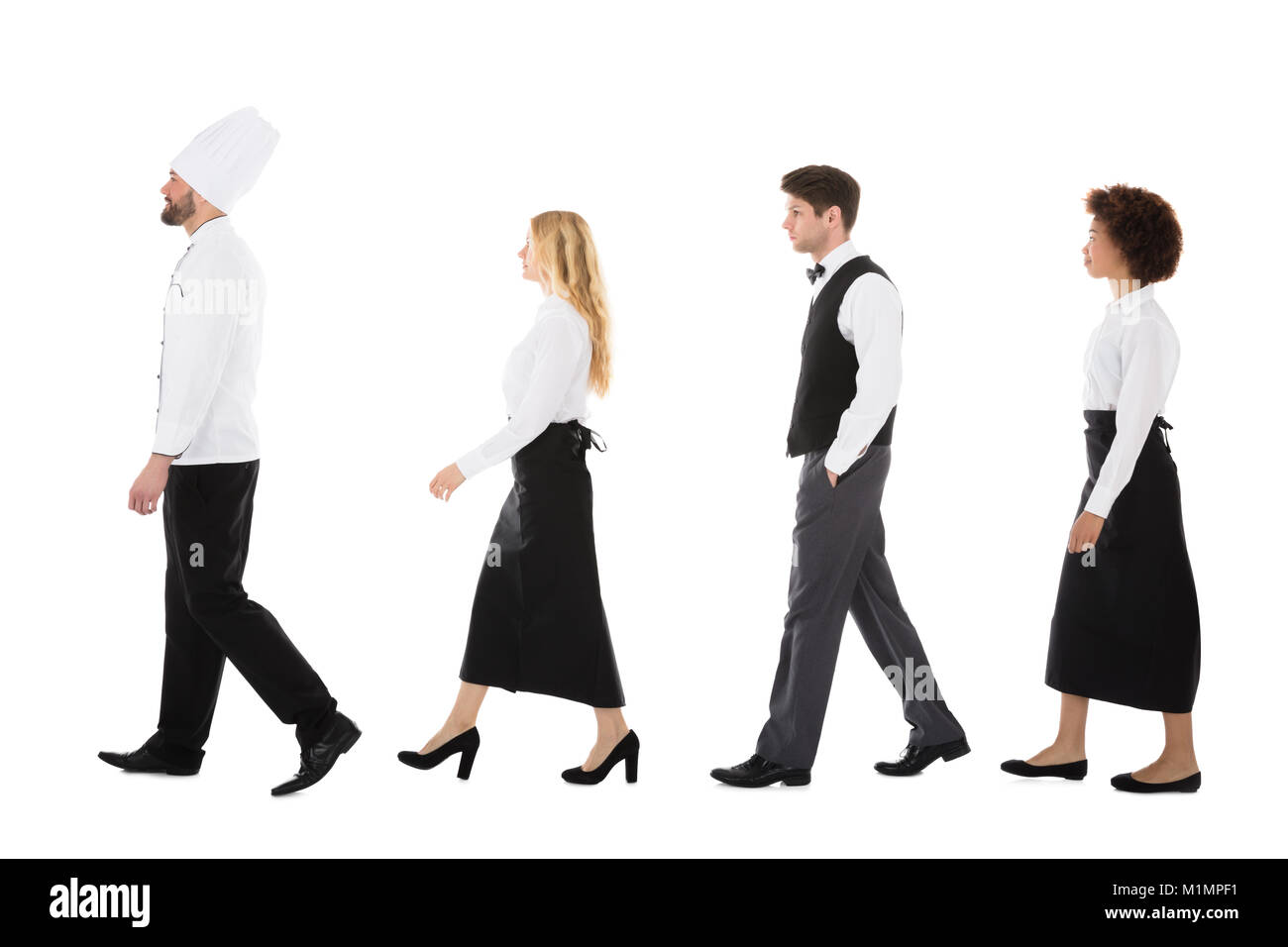 Young Restaurant Staff Walking In Row Against White Background Stock Photo