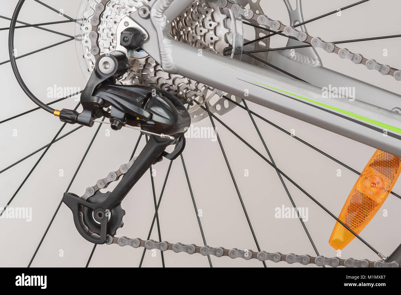 Close up of 9-speed cassette and rear derailleur on rear wheel of bike,  studio photo. - Stock Image
