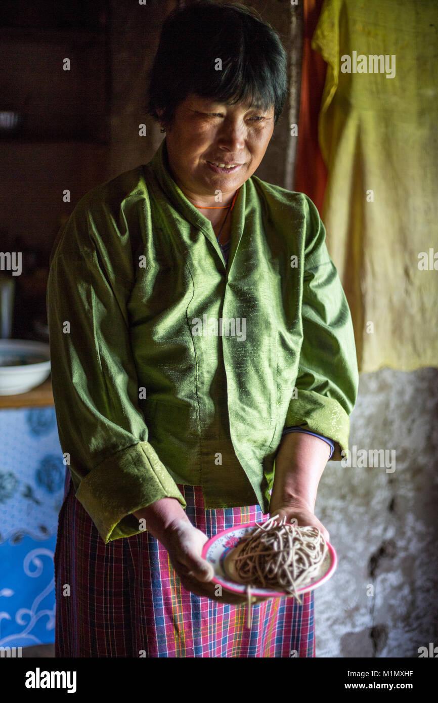 Bumthang, Bhutan.  Woman Displaying Freshly-made Buckwheat Noodles. - Stock Image