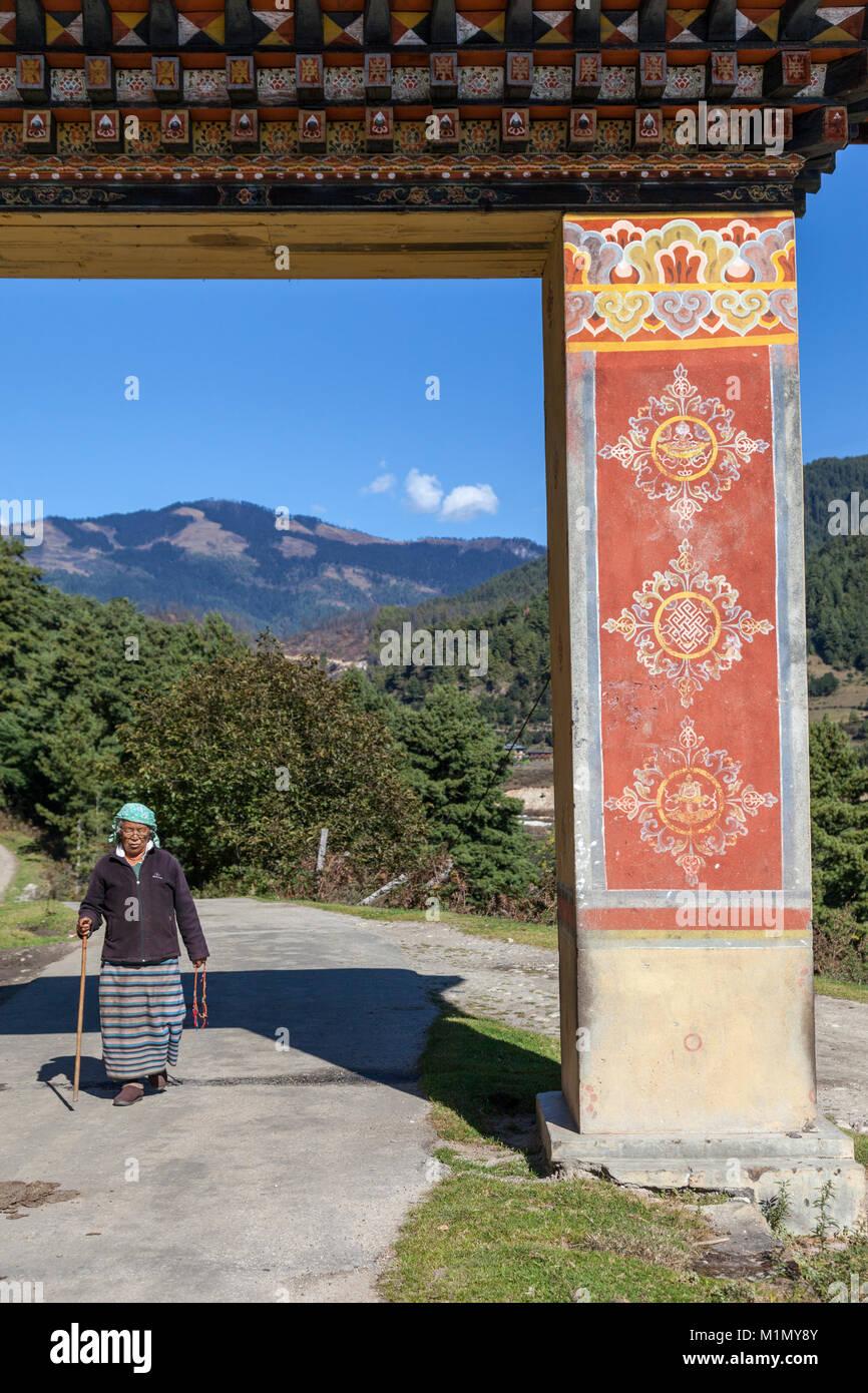 Bumthang, Bhutan.  Old Woman Entering the Gate of Kurje Lhakhang Temple. - Stock Image