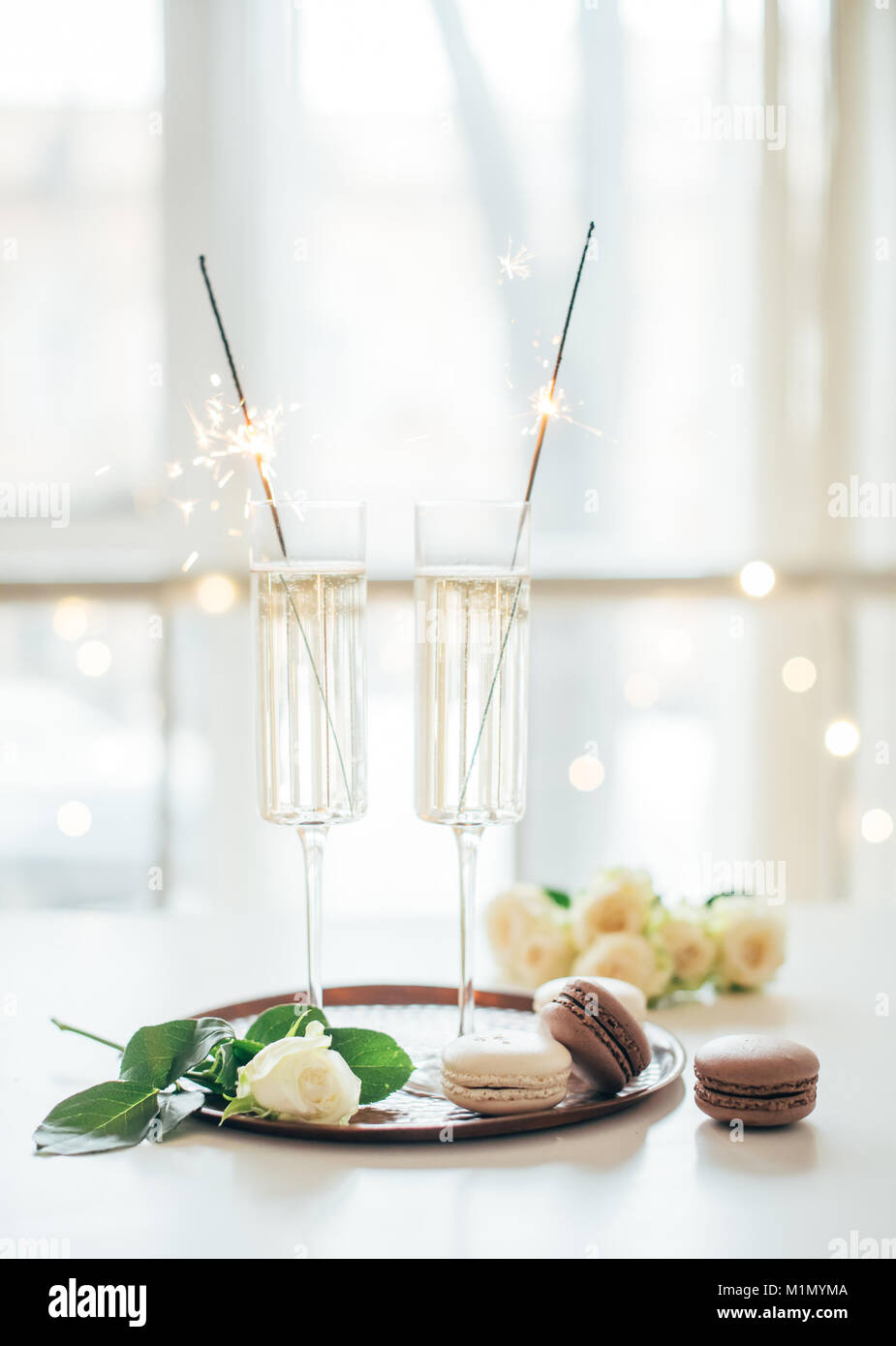 Luxurious champagne wedding party with white roses and macaron d - Stock Image