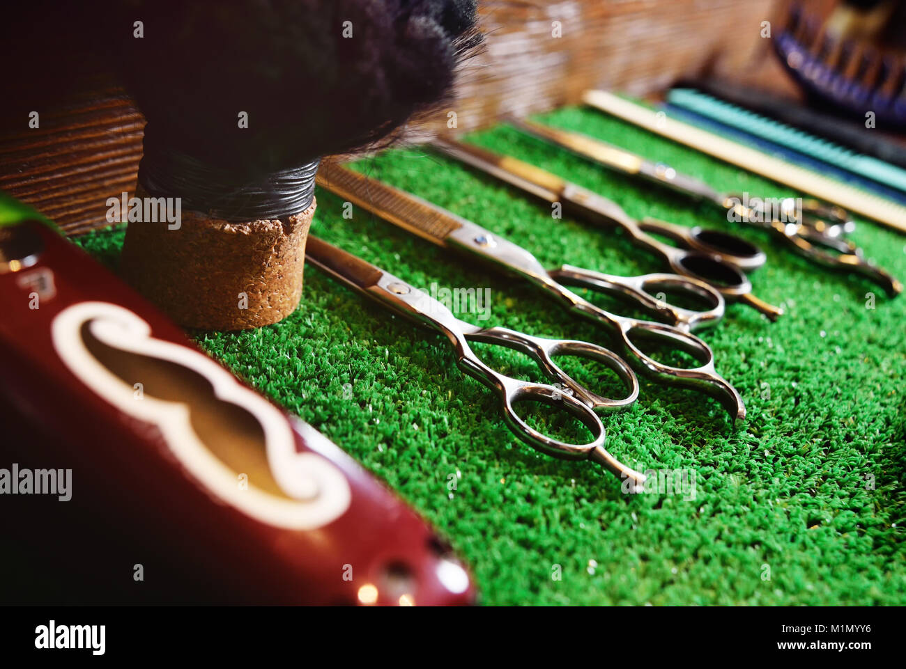 scissors for cutting on a green mat in barbershop - Stock Image