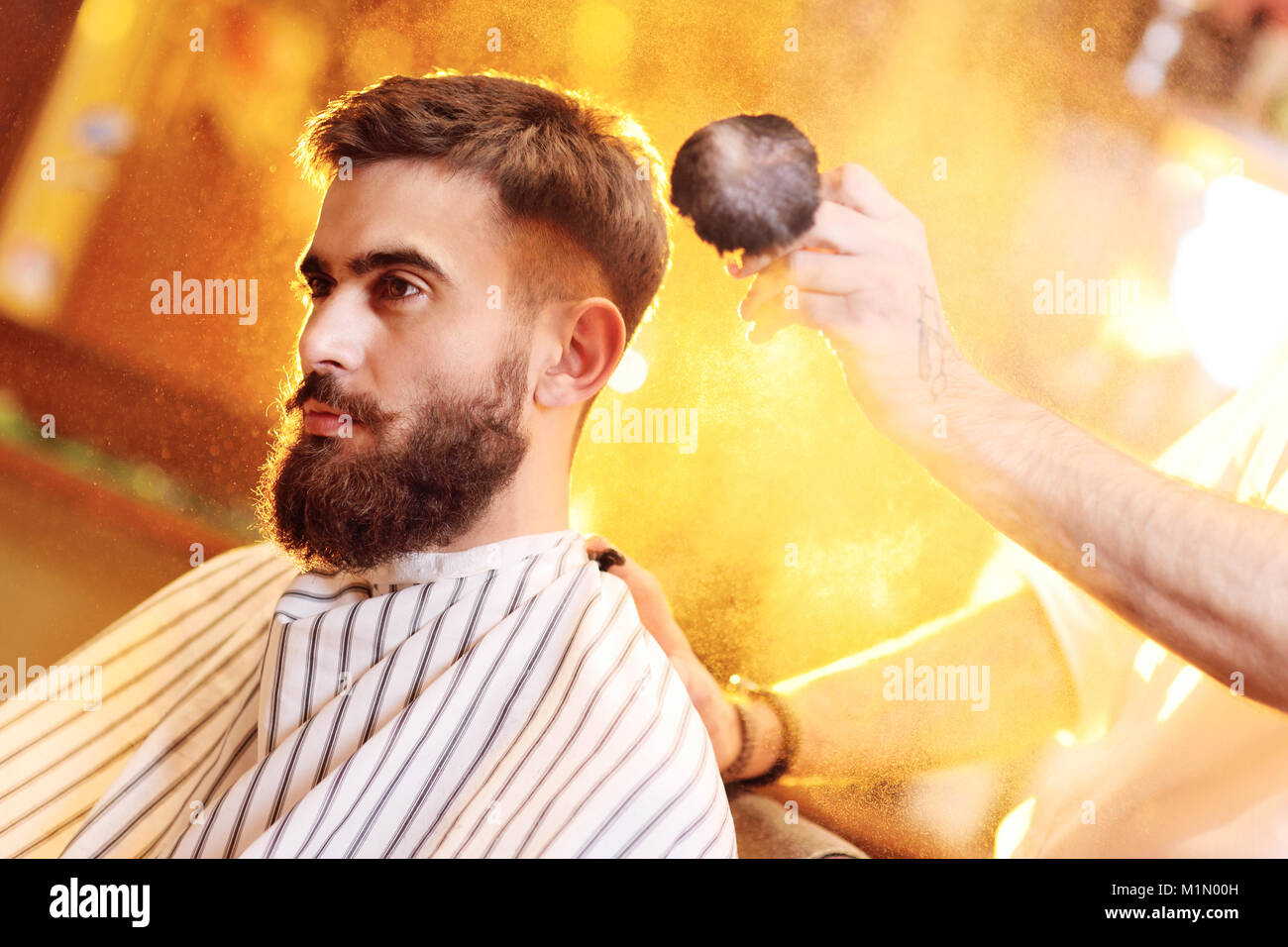 barber does a haircut for a young handsome man with a beard and mustache  - Stock Image