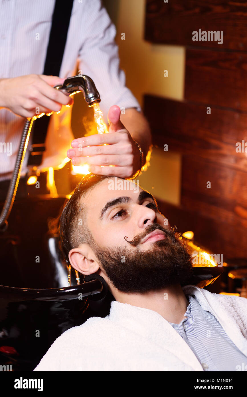 Hairdresser man washes client - Stock Image