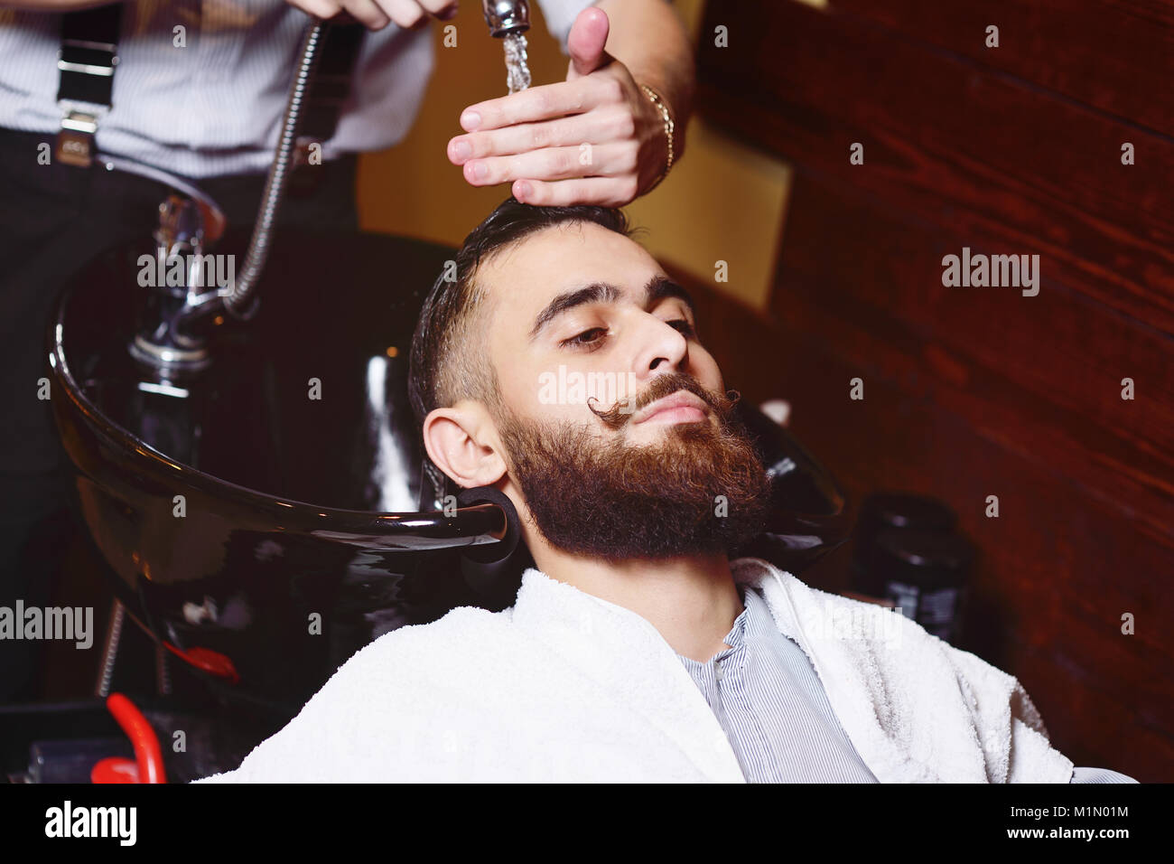 Barber or hairdresser washes the head of the client - Stock Image