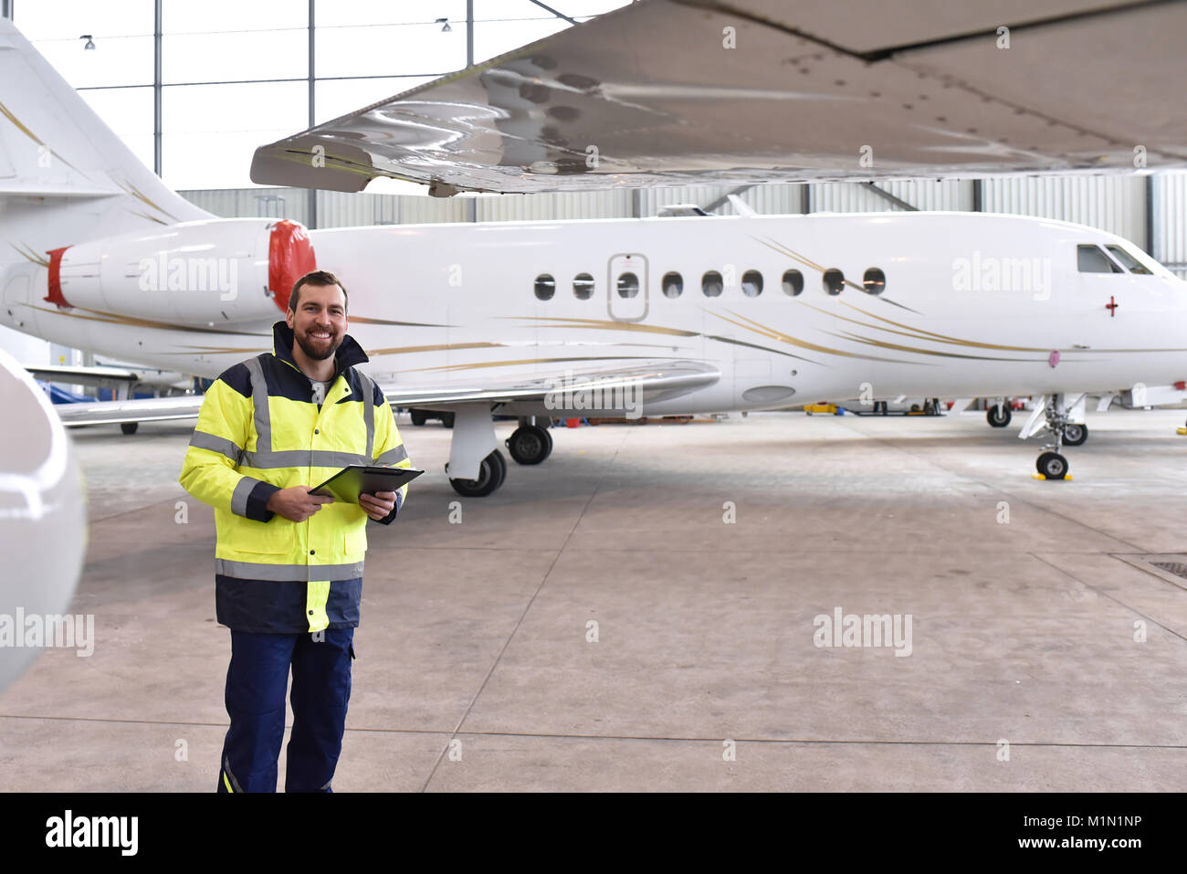 Portrait of an aircraft mechanic in a hangar with jets at the airport - Checking the aircraft for safety and technical - Stock Image