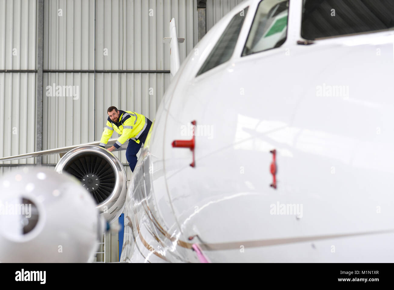 Airport workers check an aircraft for safety in a hangar - Stock Image