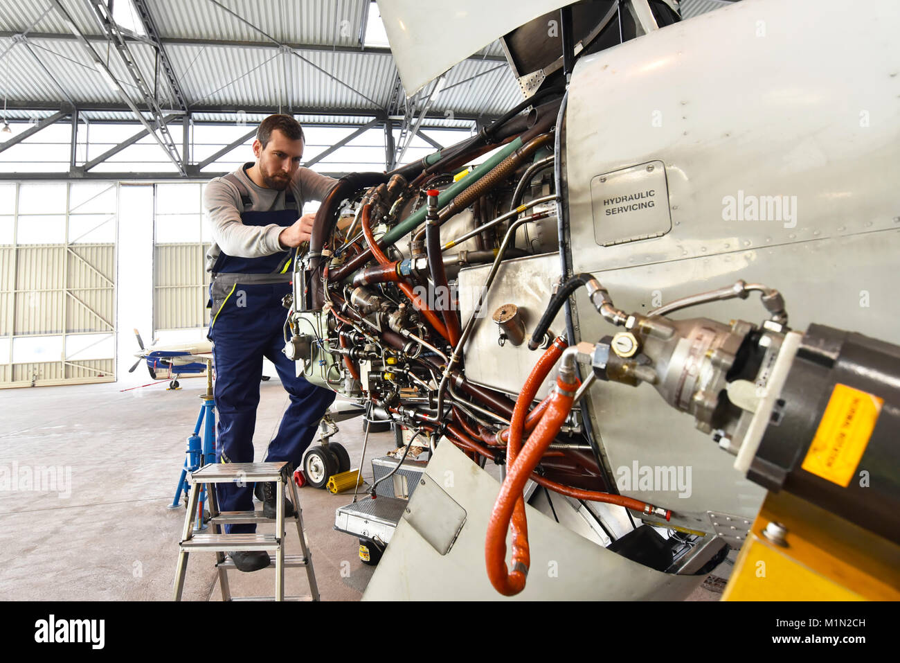 Aircraft mechanic repairs an aircraft engine in an airport hangar - Stock Image