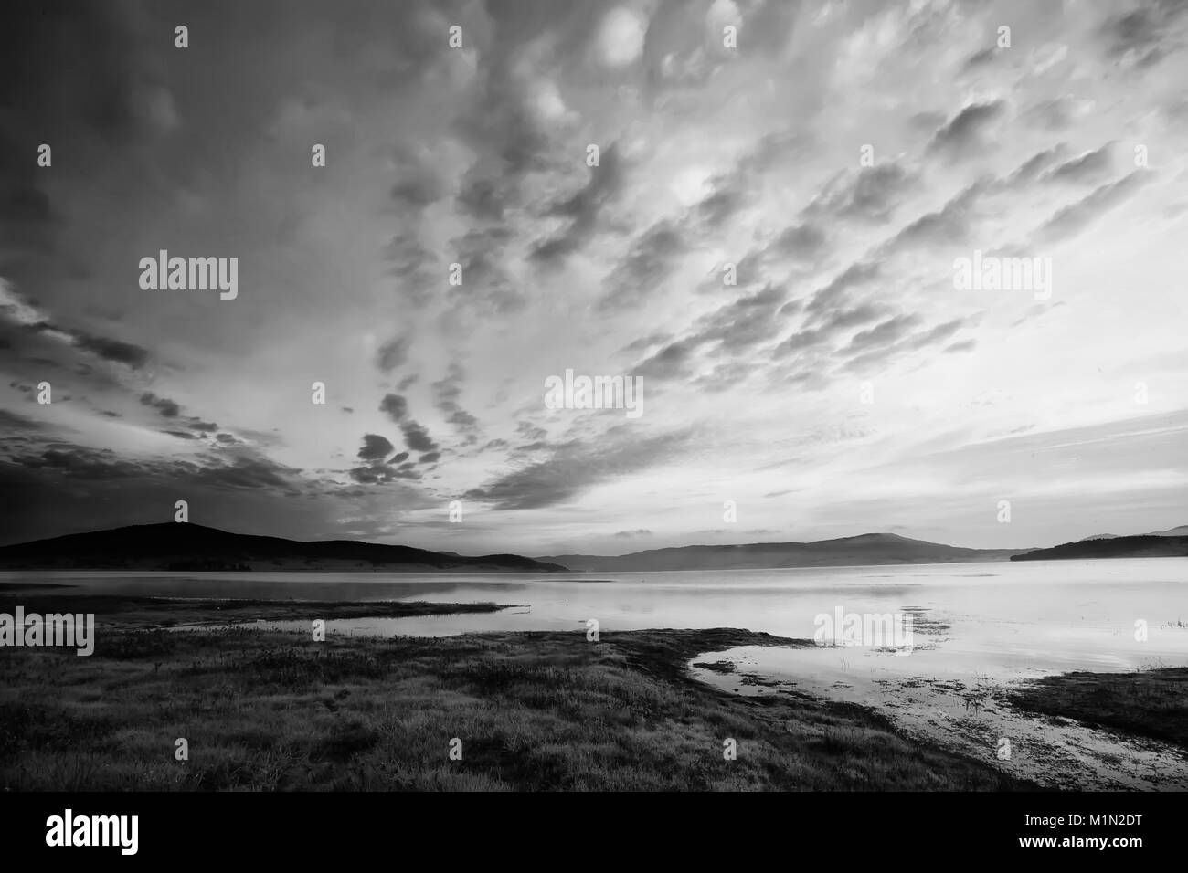 black and white high contrasted sky above the mountain lake Stock Photo