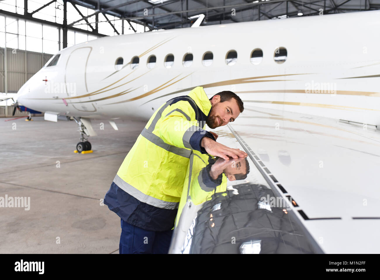 Aircraft mechanic inspects and checks the technology of a jet in a hangar at the airport - Stock Image