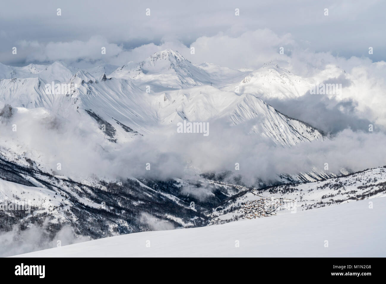 distant view across a snowy belleville valley to the ski resort of
