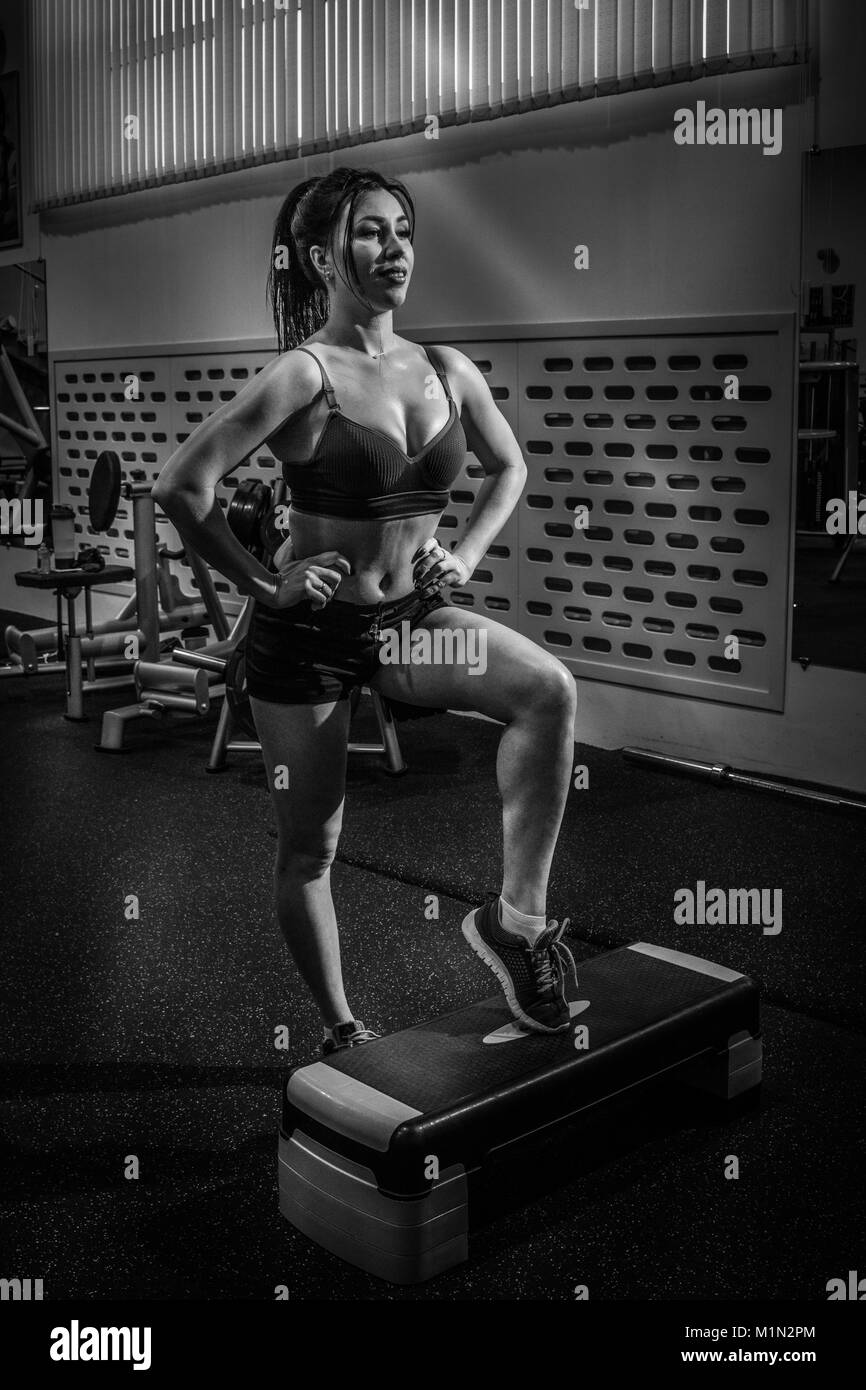 Beautiful brunette is practicing step aerobics in the gym. bw - Stock Image