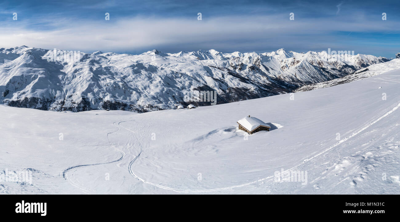 Panoramic view of barns and mountain huts in the Belleville Valley in the 3 valleys ski area of France following - Stock Image