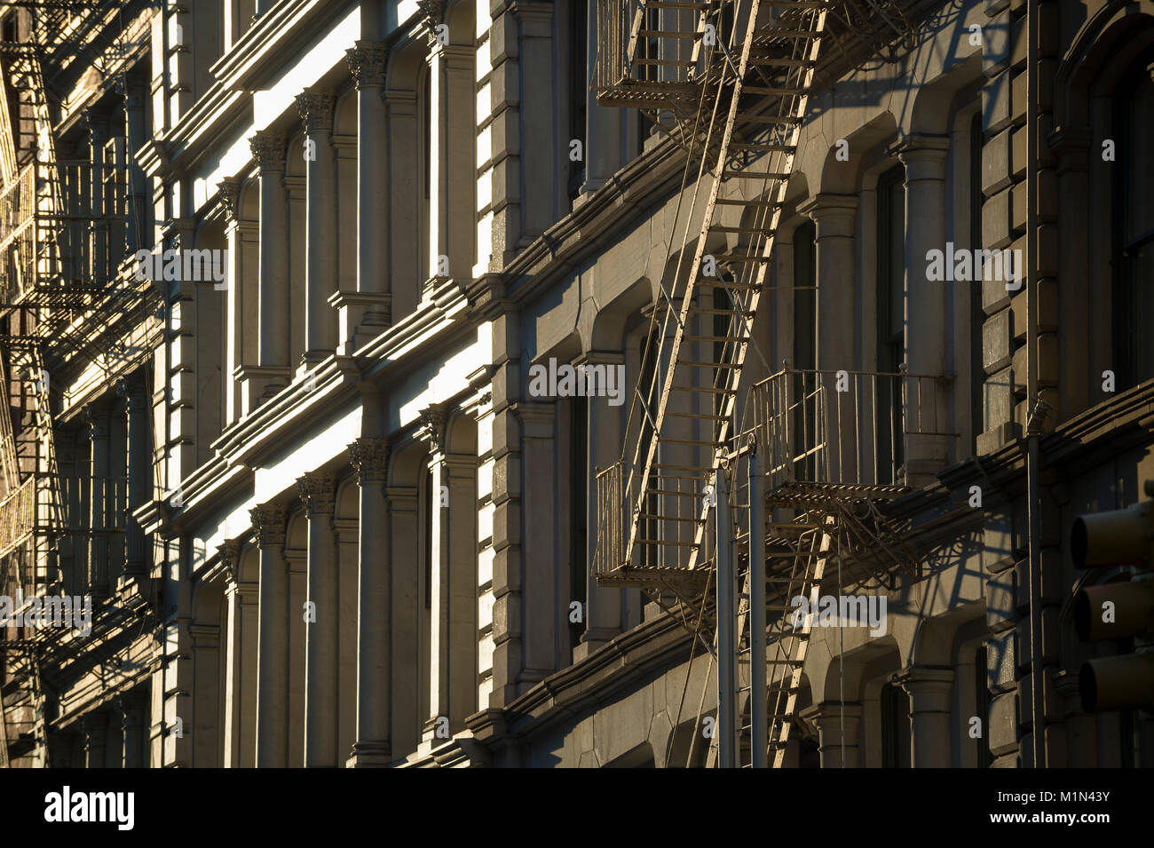 Close-up of fire escapes running down the facades of iconic cast iron buildings in Soho, New York City - Stock Image