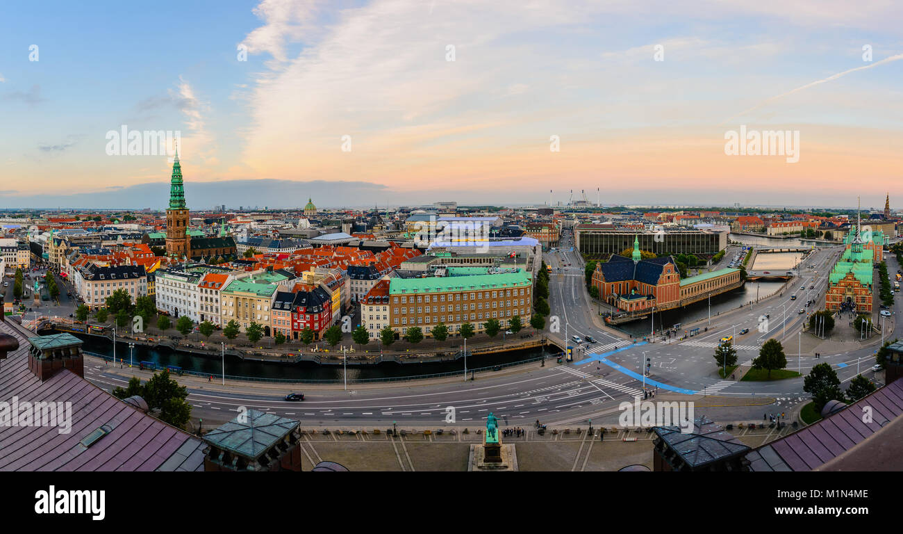 Panoramic view of evening Copenhagen streets, house roofs, canal water, Spiel of Nikolaj Church and Amalienborg - Stock Image