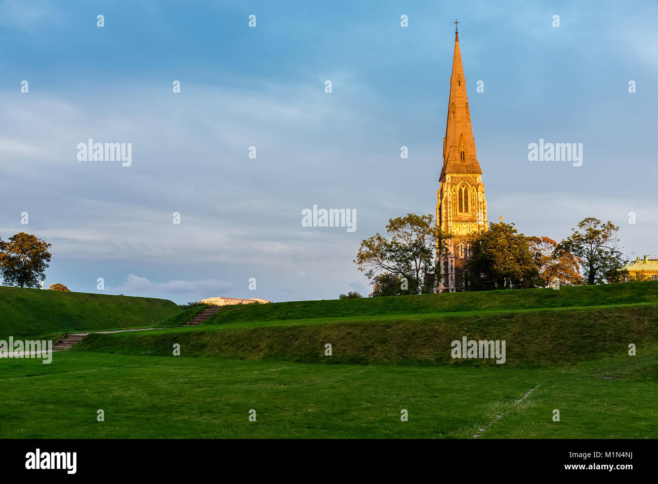 St. Alban's Church spiel colored in gold by sunset. Golden hour in Copenhagen, Denmark. - Stock Image