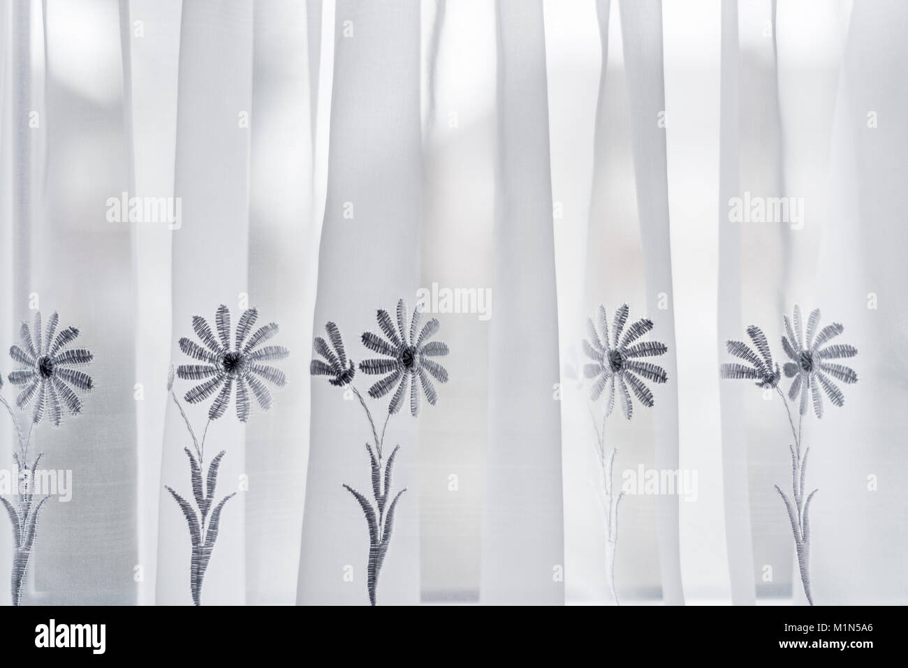 White net curtains, with floral design. Domestic translucent drapery. - Stock Image