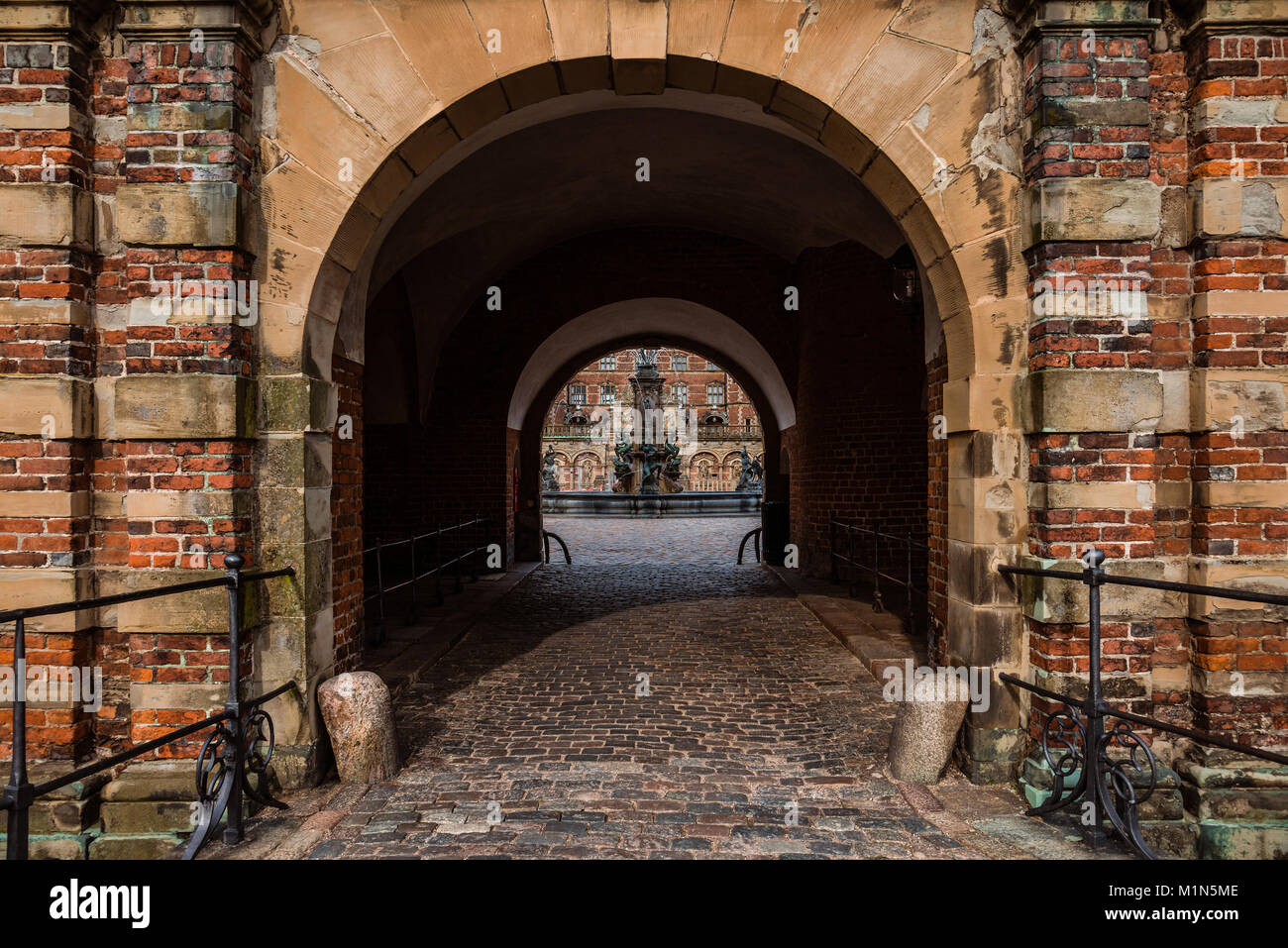 Hillerod, Denmark - September, 23th, 2015. Gateway entrance to Frederiksborg palace near Copenhagen. Arch and red - Stock Image