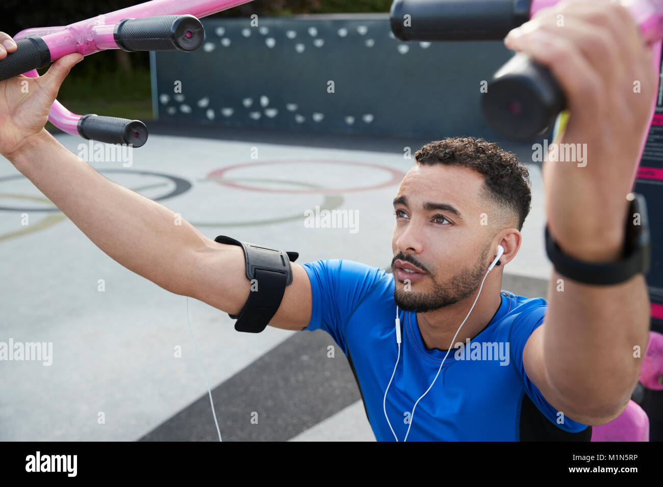 Young male athlete using outdoor gym in park, close up - Stock Image