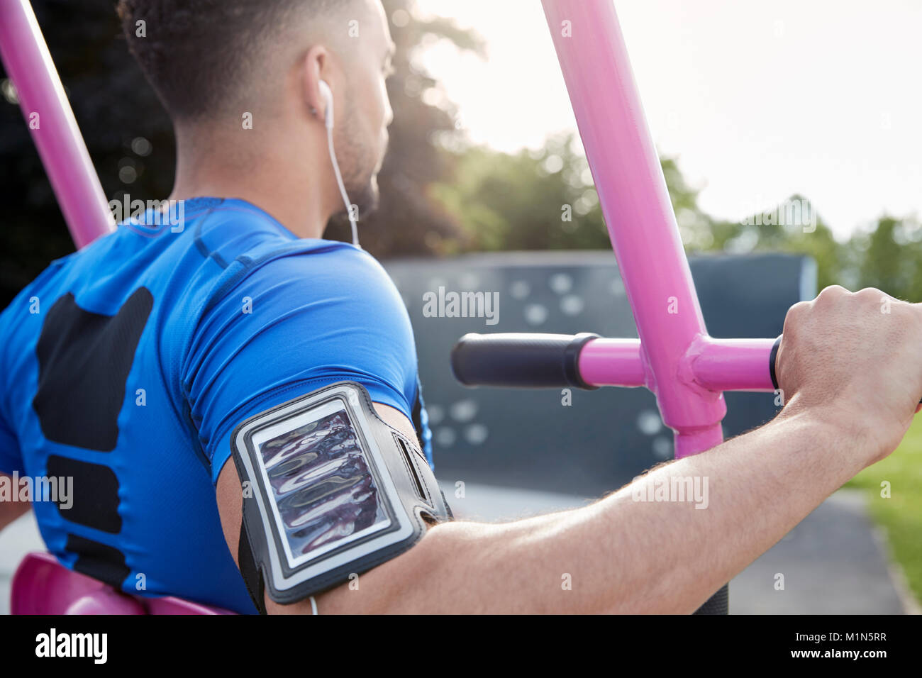 Young male athlete using outdoor gym, over shoulder view - Stock Image