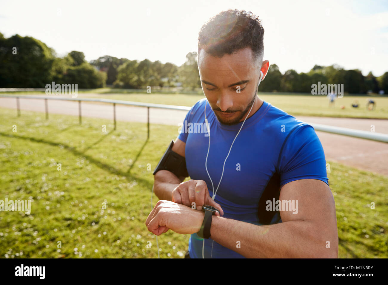 Young man at running track setting fitness app on smartwatch - Stock Image