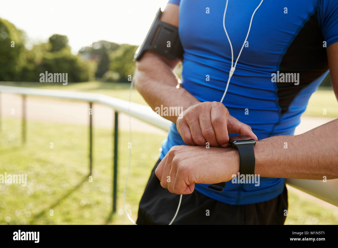 Man at track setting fitness app on smartwatch, mid section Stock Photo
