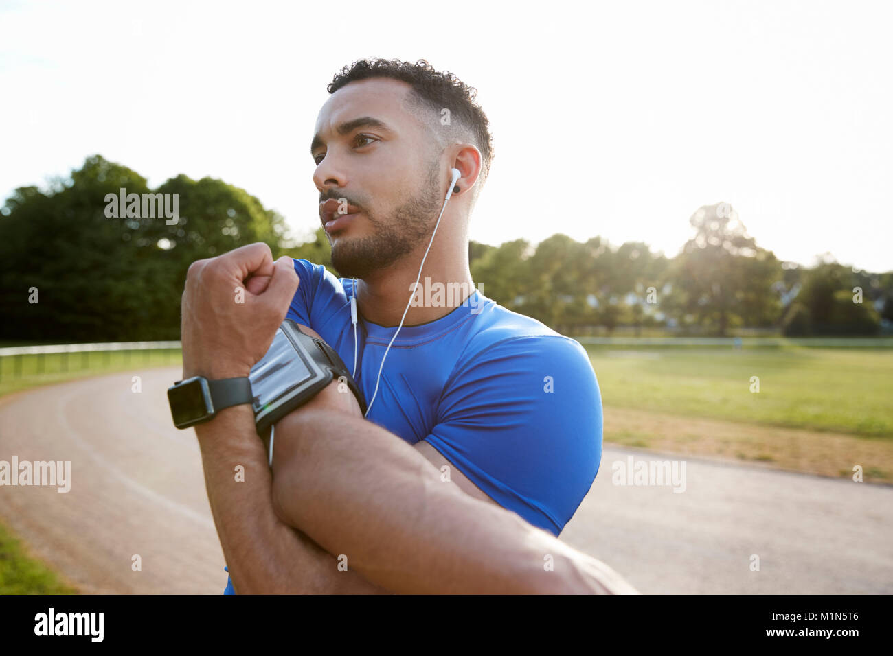 Male athlete at track stretching shoulders, close up - Stock Image