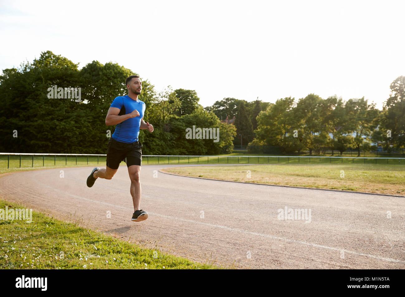 Young male athlete running at a track, full length - Stock Image