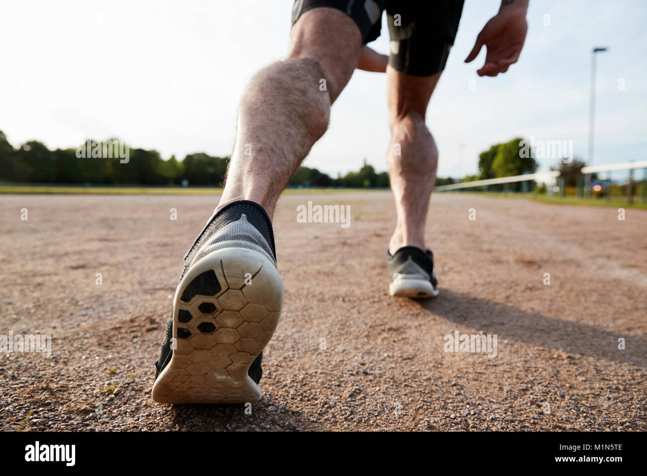 Low section of male runner's legs ready to run at a track - Stock Image