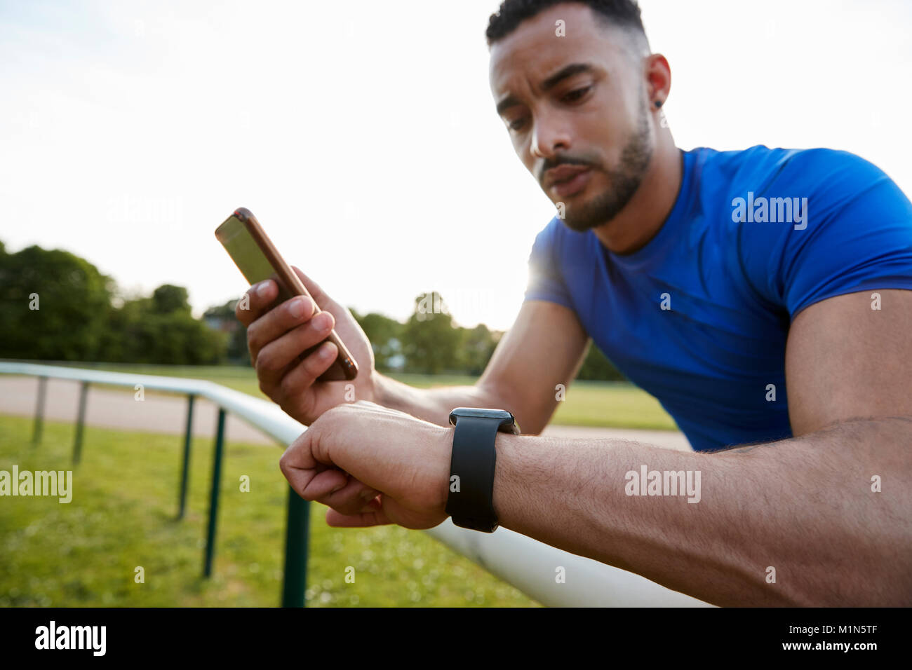 Male athlete using fitness app on smartphone and smartwatch - Stock Image